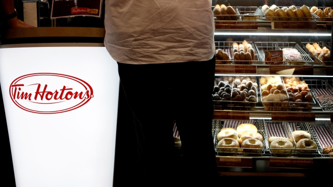 A customer places his order at a Tim Hortons in New York, Wednesday, July 22, 2009. The Canadian doughnut chain moved into 12 former Dunkin Donut locations earlier in the month, bringing new blood to the doughnut war in America's most competitive market