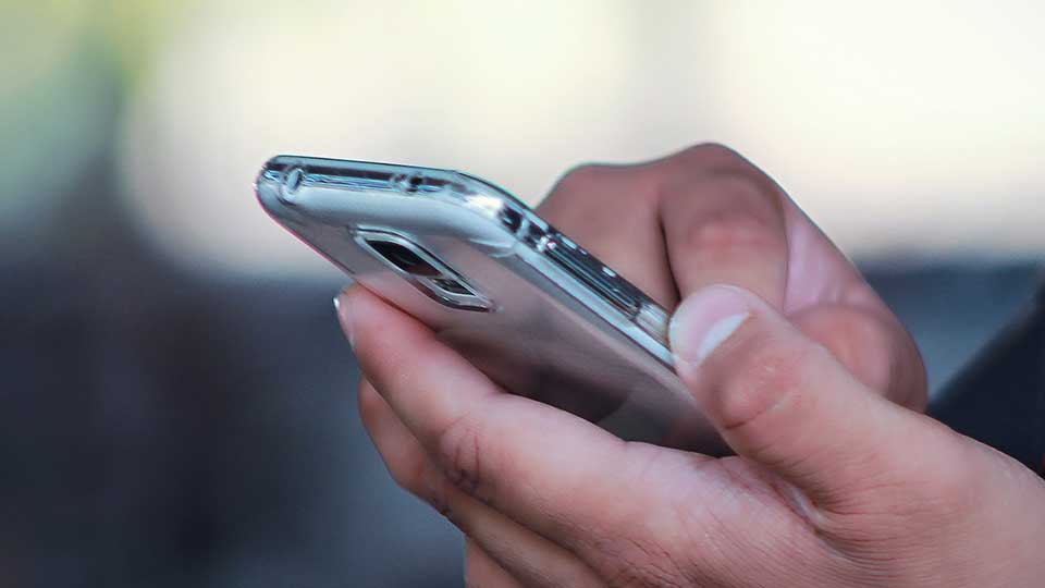 A person using a smart phone with both hands.