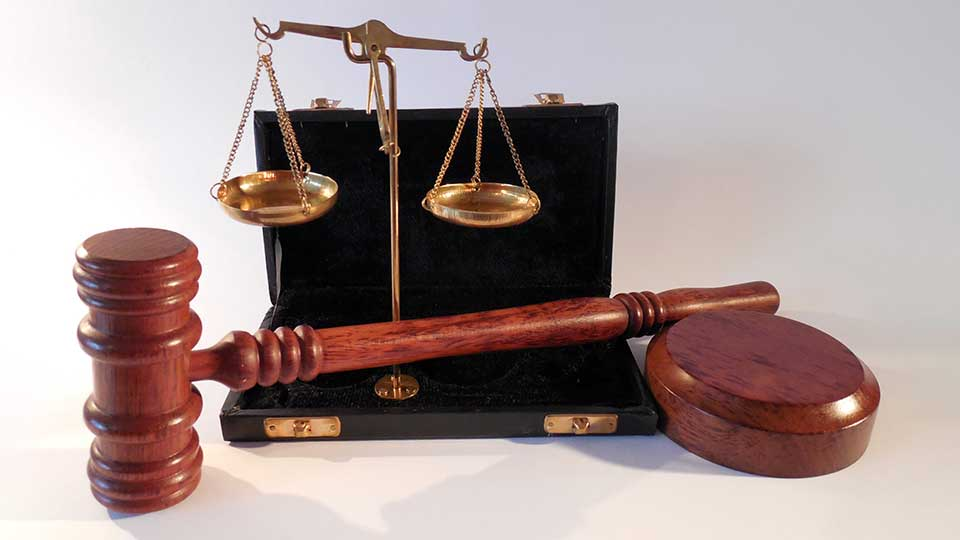 A gavel and a Scales of Justice sitting on a table.