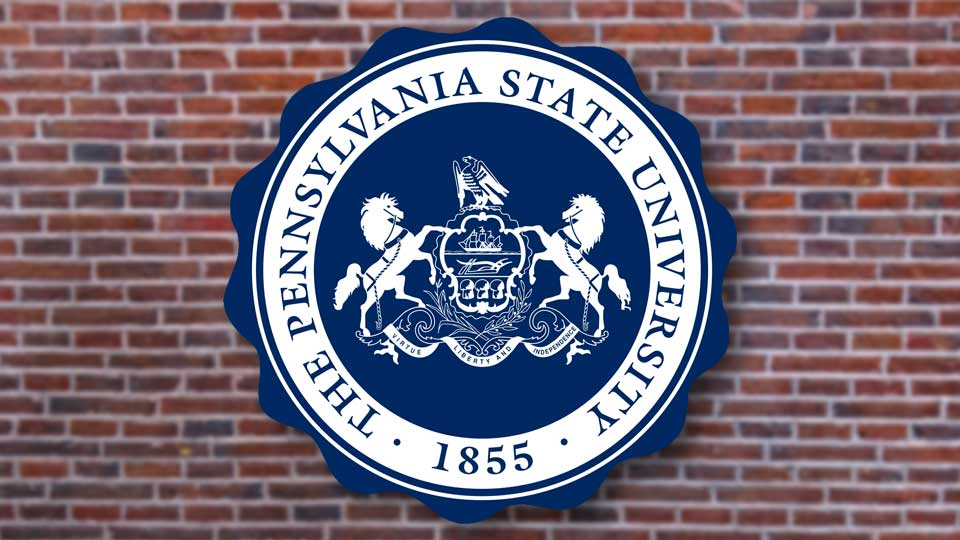 The Penn State University logo in front of a blurred brick background.