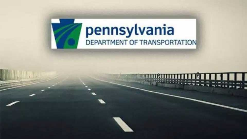 The PennDOT logo over a road.