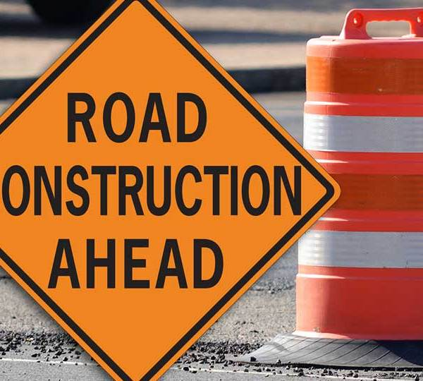 A road construction ahead sign in front of an orange construction traffic barrel.