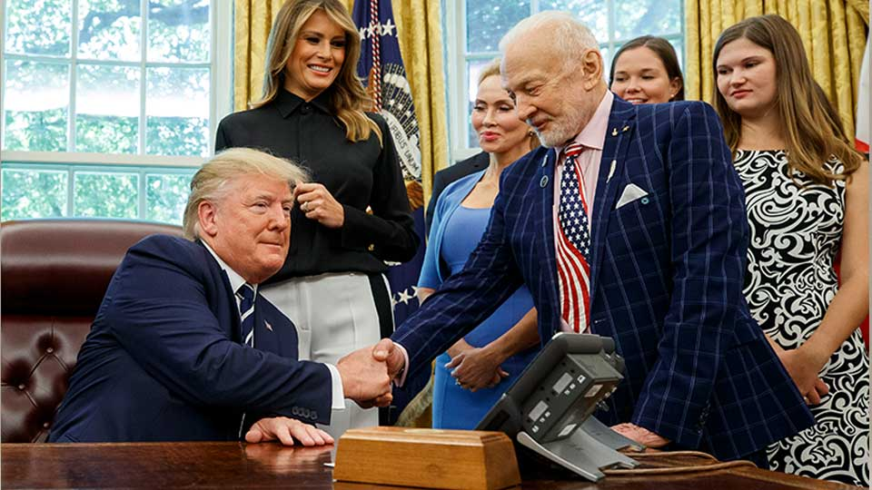 President Donald Trump shakes hands with Apollo 11 astronaut Buzz Aldrin, with first lady Melania Trump, center, during a photo opportunity commemorating the 50th anniversary of the Apollo 11 moon landing, in the Oval Office of the White House, Friday, July 19, 2019, in Washington.