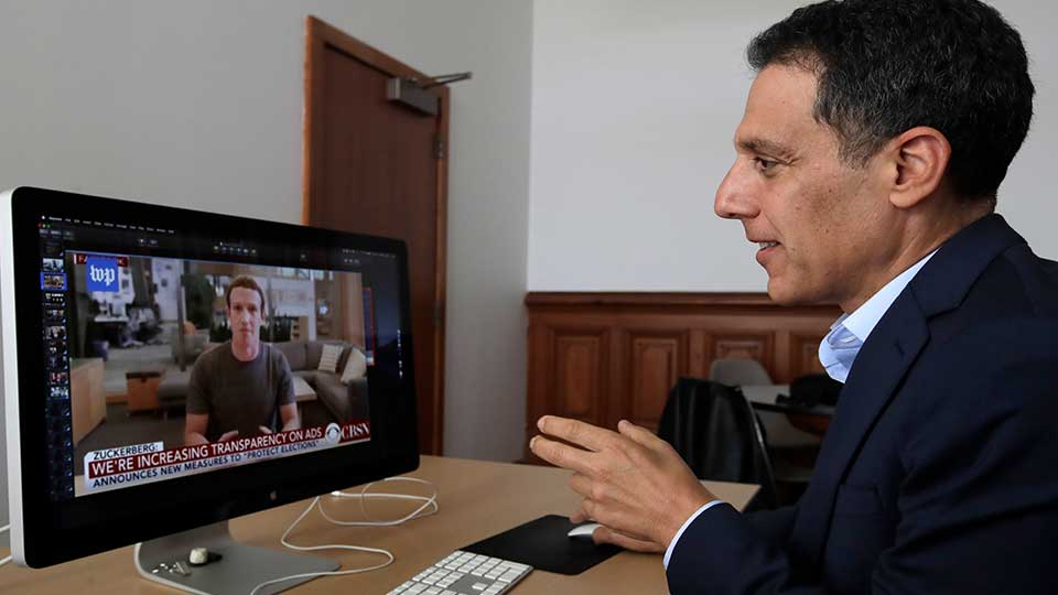 """In this Monday, July 1, 2019, photo Hany Farid, a digital forensics expert at the University of California at Berkeley, studies a video clip of Facebook CEO Mark Zuckerberg in his office in Berkeley, Calif. Sophisticated phony videos called deepfakes have attracted attention as a possible threat to election integrity. But a bigger problem for the 2020 U.S. presidential contest may be """"dumbfakes."""""""