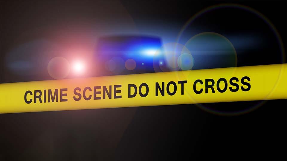 Police crime scene tape in front of police lights.