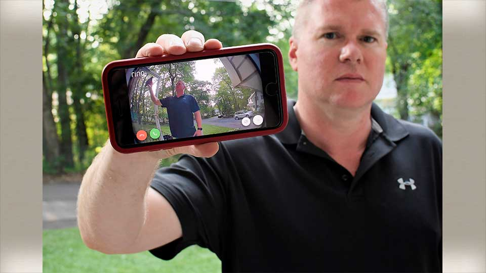 In this Tuesday, July 16, 2019, photo, Ernie Field holds up a live video of himself taken by a Ring doorbell camera at the front door at his home in Wolcott, Conn. Field won a free Ring camera and said he had to register for the app to qualify for the raffle. Now he gets alerts on his phone when a car drives by and a 30-second video when his daughter gets home from school.