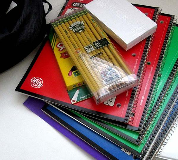 School supplies, pencils, notebooks and a book bag sitting on a desk.