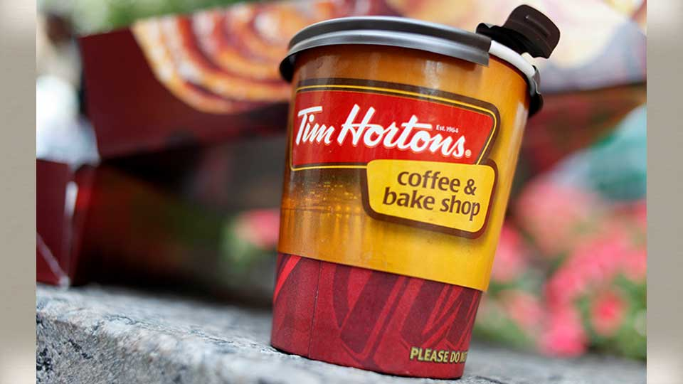 A Tim Hortons' coffee cup is seen in New York, Wednesday, July 22, 2009. The Canadian doughnut chain moved into 12 former Dunkin Donut locations earlier in the month, bringing new blood to the doughnut war in America's most competitive market.
