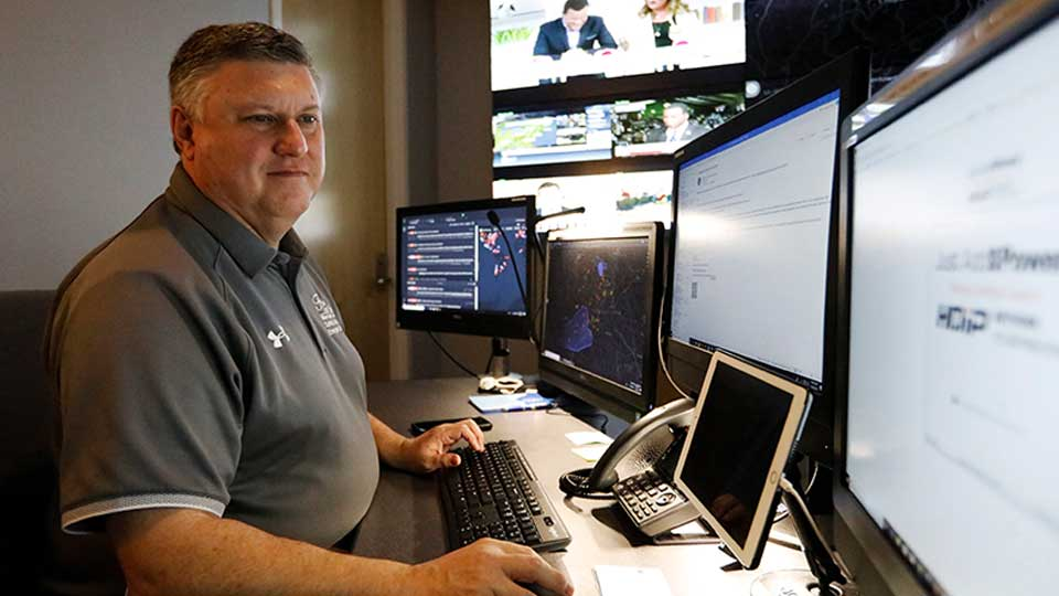 In this July 30, 2019, photo, Paul Hildreth, emergency operations coordinator for the Fulton County School District, works in the emergency operations center at the Fulton County School District Administration Center in Atlanta. Artificial Intelligence is transforming surveillance cameras from passive sentries into active observers that can immediately spot a gunman, alert retailers when someone is shoplifting and help police quickly find suspects. Schools, such as the Fulton County School District, are among the most enthusiastic adopters of the technology.