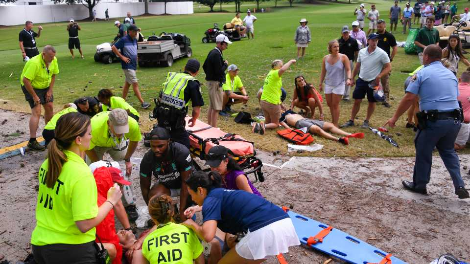 Spectators are tended to after a lightning strike on the course which left several injured during a weather delay in the third round of the Tour Championship golf tournament Saturday (AP Photo/John Amis)