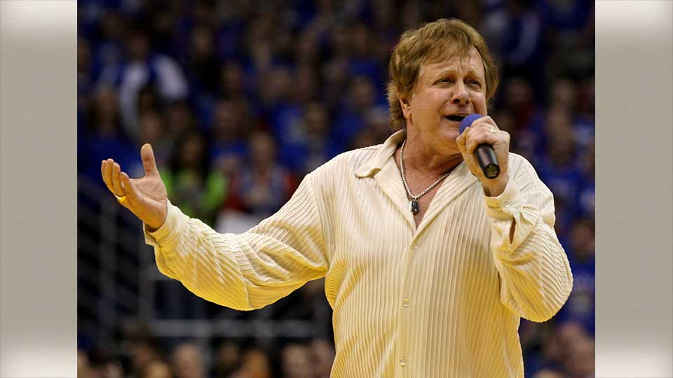 "FILE - In this Jan. 25, 2010 file photo, Eddie Money sings the national anthem before an NCAA college basketball game between Kansas and Missouri in Lawrence, Kan. Eddie Money says he has stage 4 esophageal cancer. The singer known for such hits as ""Two Tickets to Paradise"" and ""Take Me Home Tonight"" says his fate is in ""God's hands."" Money's comments appear in a video released Saturday, Aug. 24, 2019 from his AXS TV reality series ""Real Money."" The full episode airs Sept. 12.(AP Photo/Charlie Riedel, File)"