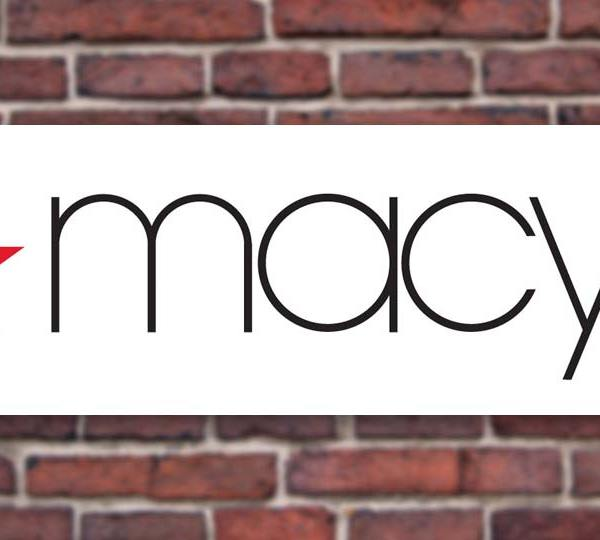 The Macy's logo in front of a brick wall.