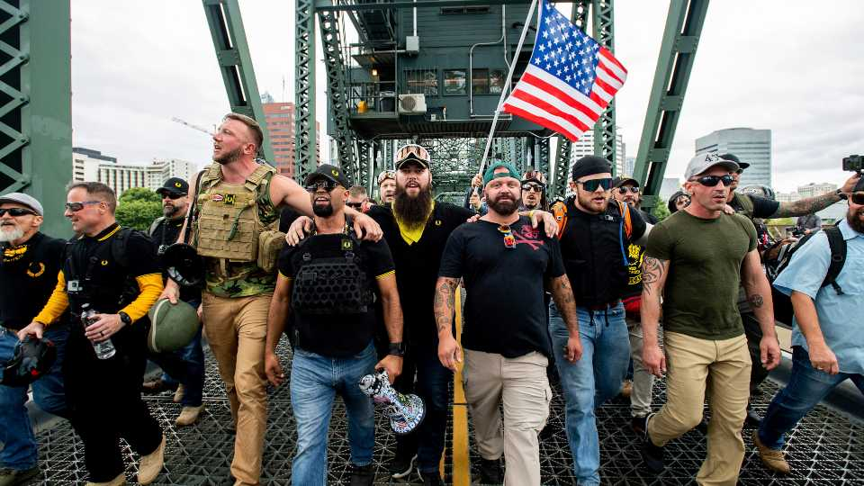 "Members of the Proud Boys and other right-wing demonstrators march across the Hawthorne Bridge during an ""End Domestic Terrorism"" rally in Portland, Oregon (AP Photo/Noah Berger)"
