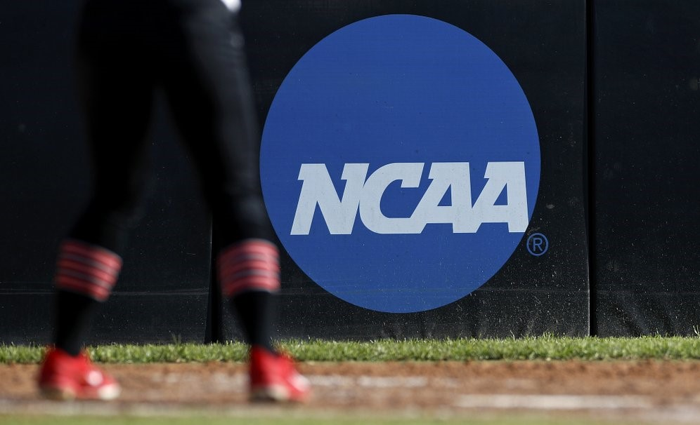 FILE - In this April 19, 2019, file photo, an athlete stands near a NCAA logo during a softball game in Beaumont, Texas. California will let college athletes hire agents and make money from endorsements, defying the NCAA and setting up a likely legal challenge that could reshape U.S. amateur sports.