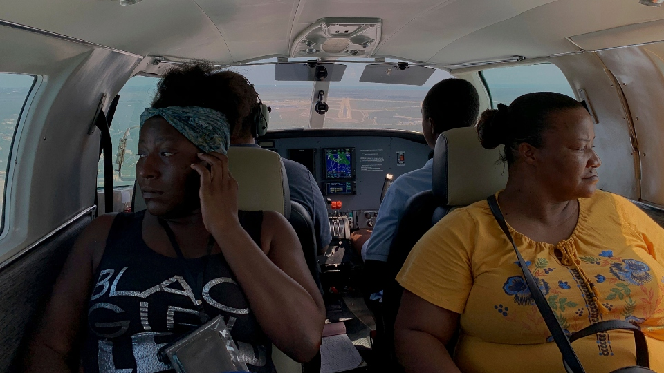 Dimple Lightbourne, left, and her mother Carla Ferguson sit in a plane as it approaches to land in Nassau after they were evacuated from Abaco Island, in the Bahamas (AP Photo/Fernando Llano)