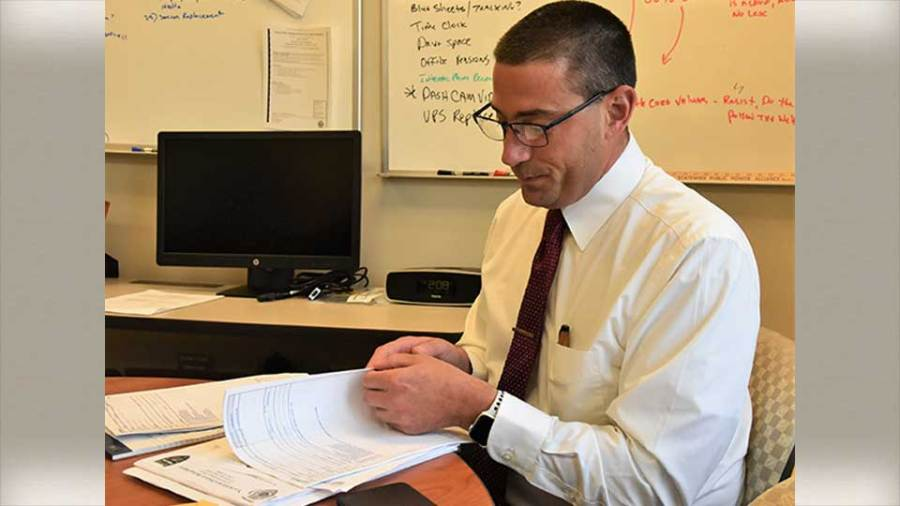 Lt. Brian Butler of the Youngstown Police Department sifts through reports at the Hubbard Police Department written by a candidate who works for Hubbard who applied to work in Youngstown. Butler wanted to see what kinds of reports the officer generates as well as how they are written.