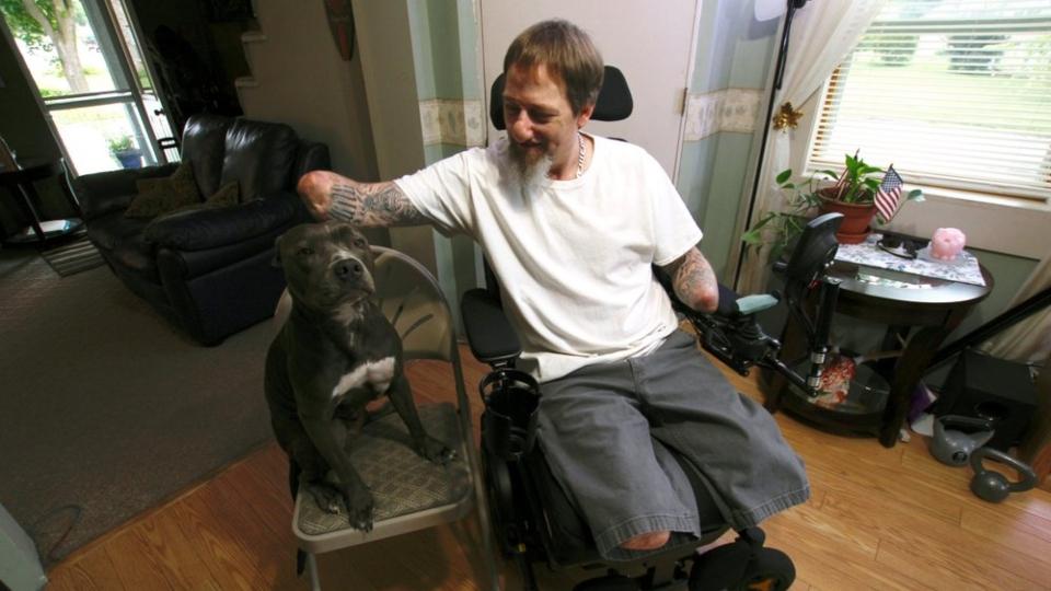 Greg Manteufel pets his dog Ellie