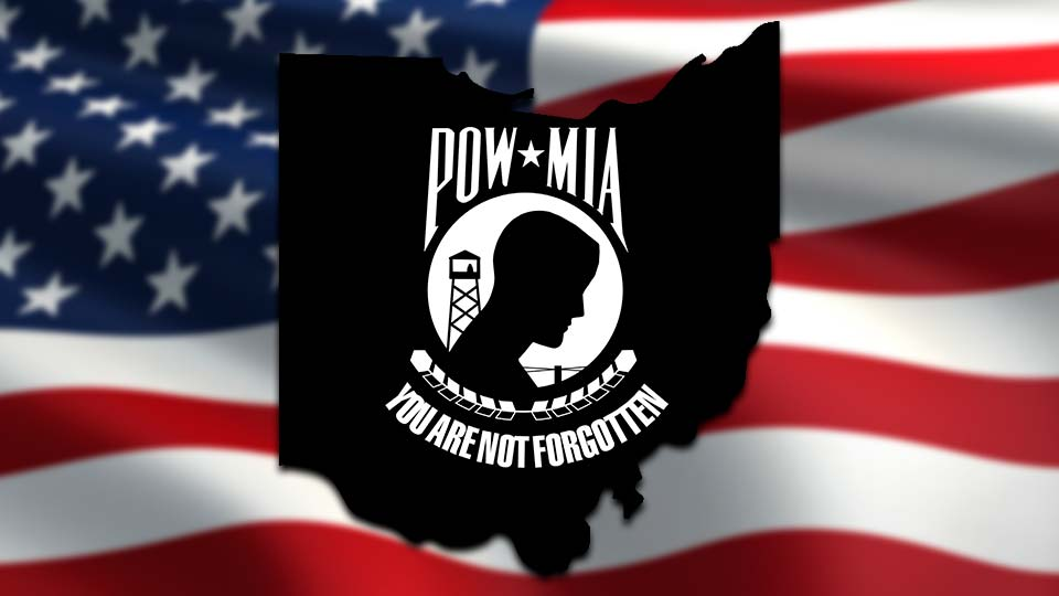 The POW/MIA Flag in the shape of Ohio, over an American flag.