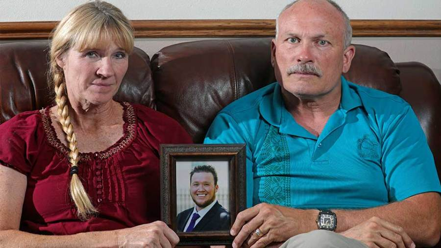In this Monday, Sept. 9, 2019, photo, Rod and Tonya Meldrum hold a portrait of their son Devin Meldrum, in Provo, Utah. He suffered from debilitating cluster headaches and fatally overdosed after taking a single fentanyl-laced counterfeit oxycodone pill purchased from a dark-web store run by Aaron Shamo, according to his family and authorities. Shamo was not charged in Meldrum's death, and his lawyers have argued that and other alleged overdoses can't be definitively linked to him.
