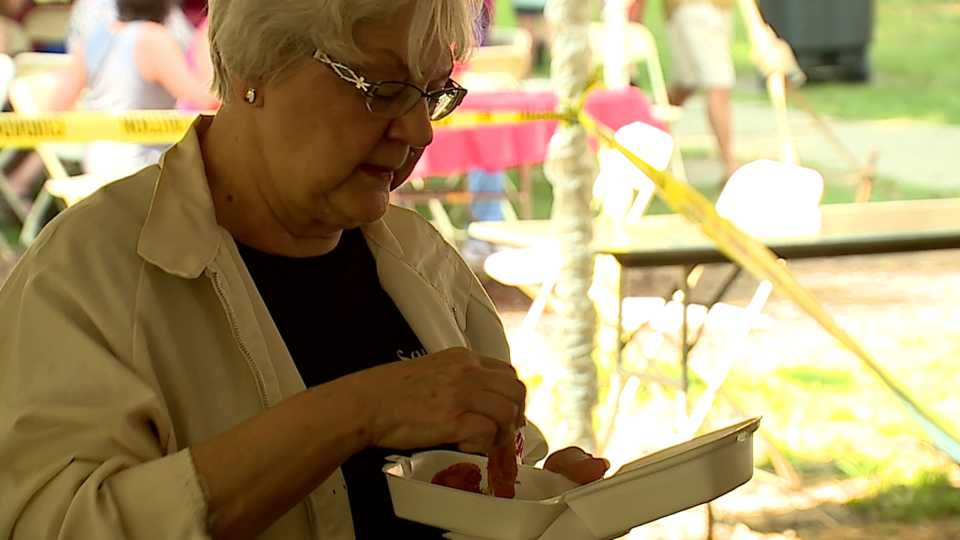 Woman eating at the Taste of Warren event.