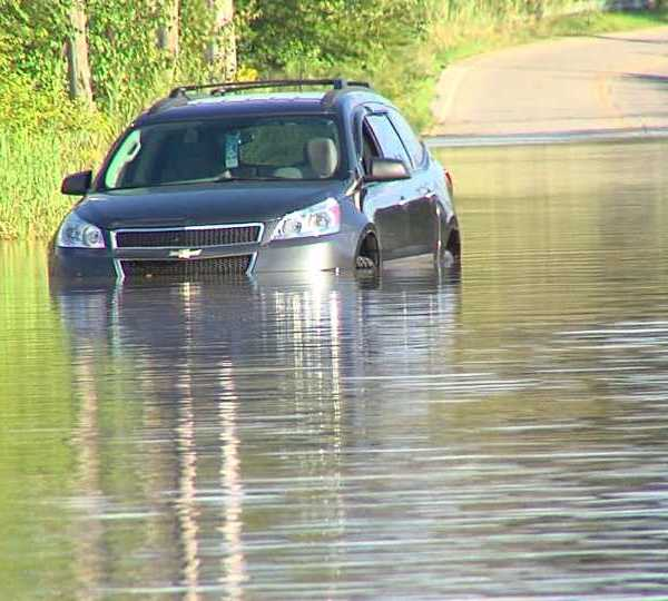 Tow truck driver helps elderly man from Niles out of car on flooded Warren road.