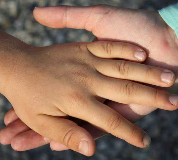 Photo of holding a child's hand, child support.