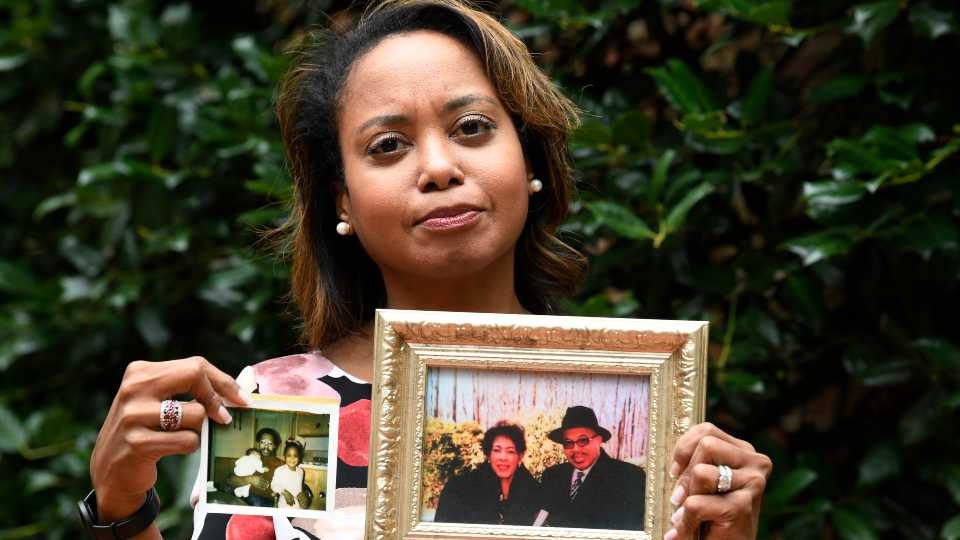 Donna Cryer holds up family photos that include her father Roland Henry, as she poses for a photo in Washington. (AP Photo/Susan Walsh).