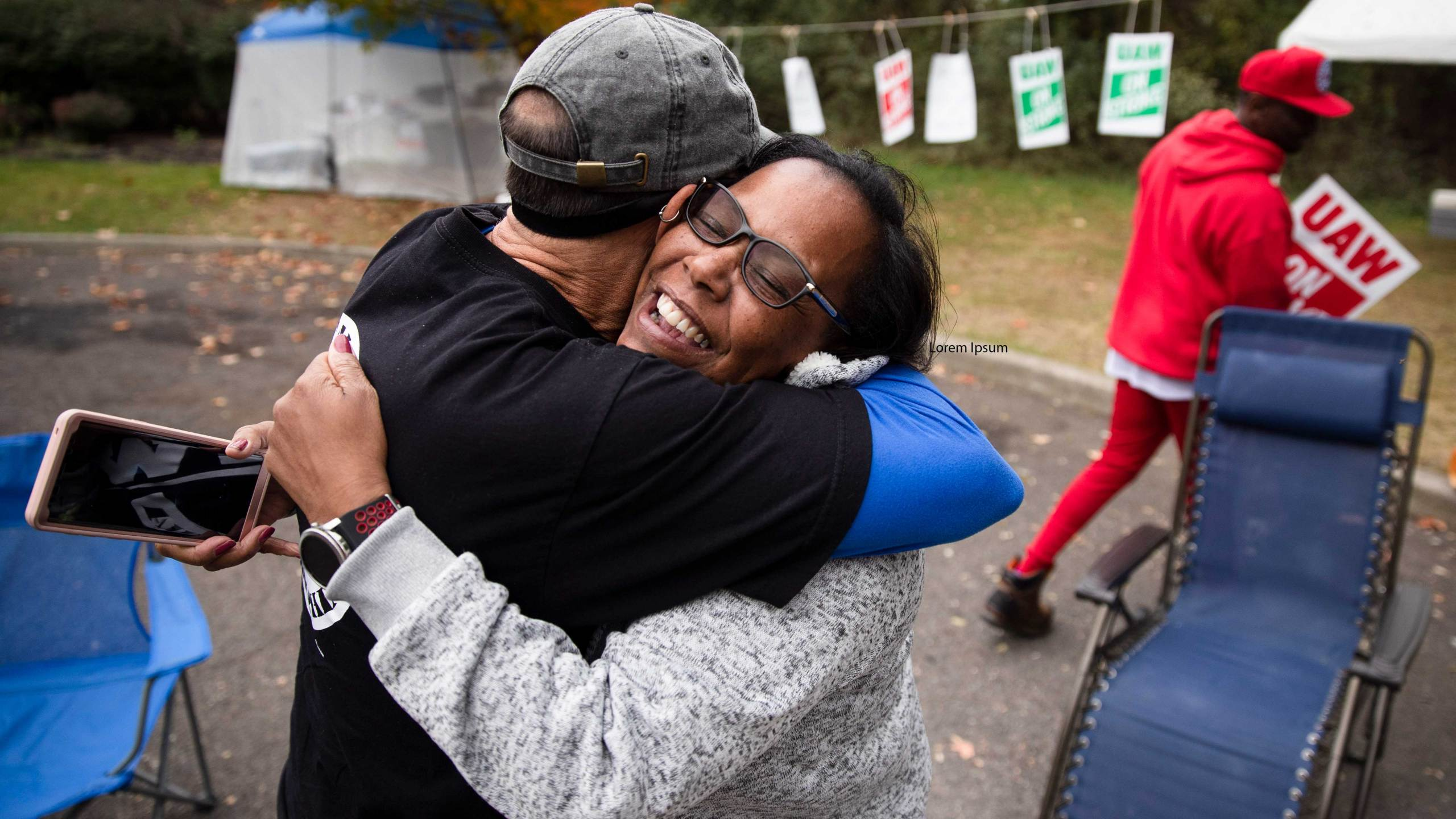 Picketing United Auto Workers Richard Rivera, left, and Robin Pinkney react to news of a tentative contract agreement with General Motors, in Langhorne, Pa., Wednesday, Oct. 16, 2019. Bargainers for General Motors and the United Auto Workers reached a tentative contract deal on Wednesday that could end a monthlong strike that brought the company's U.S. factories to a standstill. (