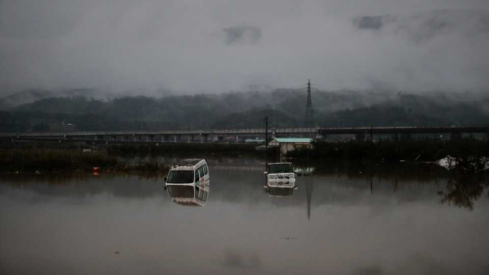 Two vehicles are submerged in floodwaters Monday, Oct. 14, 2019, in Hoyasu, Japan (AP Photo/Jae C. Hong).