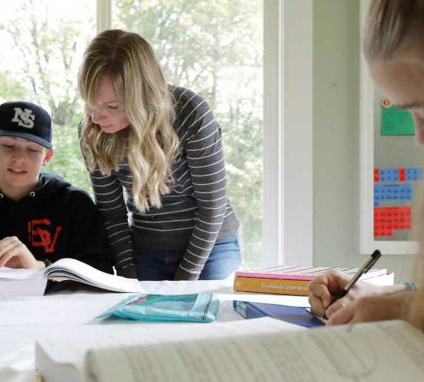 In this Oct. 9, 2019, photo, Donya Grant, center, works on a homeschool lesson with her son Kemper, 14, as her daughter Rowyn, 11, works at right, at their home in Monroe, Wash. The family joined a lawsuit against the Monroe School District and others, alleging that the district failed to adequately respond to PCBs, or polychlorinated biphenyls, at the Sky Valley Education Center, a K-12 public school. Grant has homeschooled her children since they left Sky Valley in 2016 for health reasons that they believe were related to the toxic chemicals.