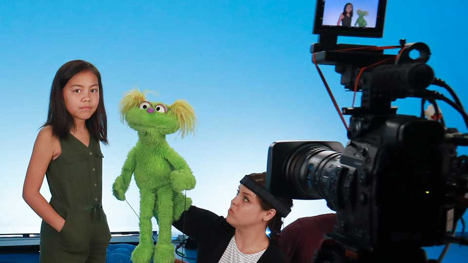 """This Aug. 6, 2019 photo shows Salia Woodbury, 10, left, from Irvine, Calif., on the set with """"Sesame Street"""" muppet Karli and puppeteer Haley Jenkins during a taping about parental addiction in New York. Sesame Workshop is addressing the issue of addiction. Data shows 5.7 million children under 11 live in households with a parent with substance use disorder. Salia's parents are in recovery after struggling with addiction and share her experience with the show's Karli—whose muppet character has a mom who is also in recovery."""