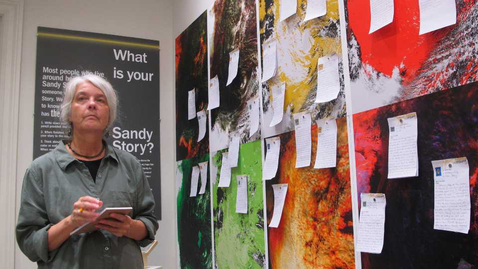 This Oct. 21, 2019 photo shows Karen Bright, a professor at Monmouth University, with a Superstorm Sandy-themed art exhibit she and another professor created in West Long Branch, N.J. Personal stories of people who survived Superstorm Sandy are an integral part of a new art exhibit remembering the deadly storm and the devastation it caused.
