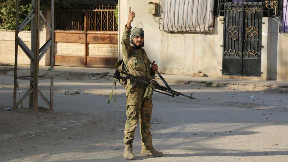 Turkey-backed Syrian fighter stand in Ras al-Yan, Syria (AP Photo).