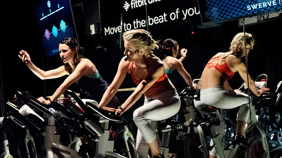 FILE - In this March 1, 2017, file photo, Jamey Powell, left, and Julianne Hough lead an exercise class as the participants are introduced to the Alta HR fitness tracker at Swerve cycling center in New York. Google's parent company is buying wearable device maker Fitbit for about $2.1 billion. Alphabet said Friday, Nov. 1, 2019, that it will pay $7.35 per share.