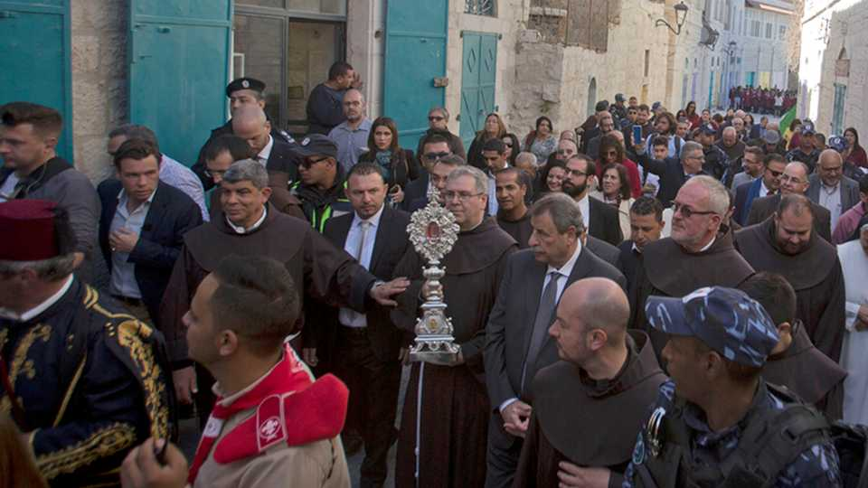 Christian clergymen carry a wooden relic believed to be from Jesus' manger outside the Church of the Nativity, traditionally believed by Christians to be the birthplace of Jesus Christ, in the West Bank city of Bethlehem, Saturday, Nov. 30, 2019. A tiny wooden relic believed to have been part of Jesus' manger has returned to its permanent home in the biblical city of Bethlehem 1,400 years after it was sent to Rome as a gift to the Pope