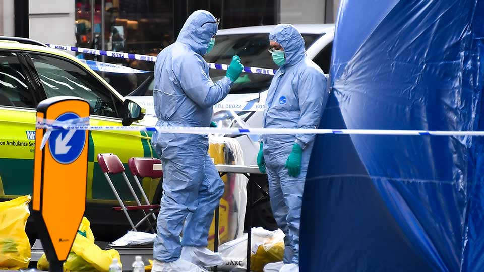 Forensic workers attend the scene on London Bridge in London, Saturday, Nov. 30, 2019. UK counterterrorism police on Saturday searched for clues into how a man imprisoned for terrorism offenses before his release last year managed to stab several people before being tackled by bystanders and shot dead by officers on London Bridge. Two people were killed and three wounded.