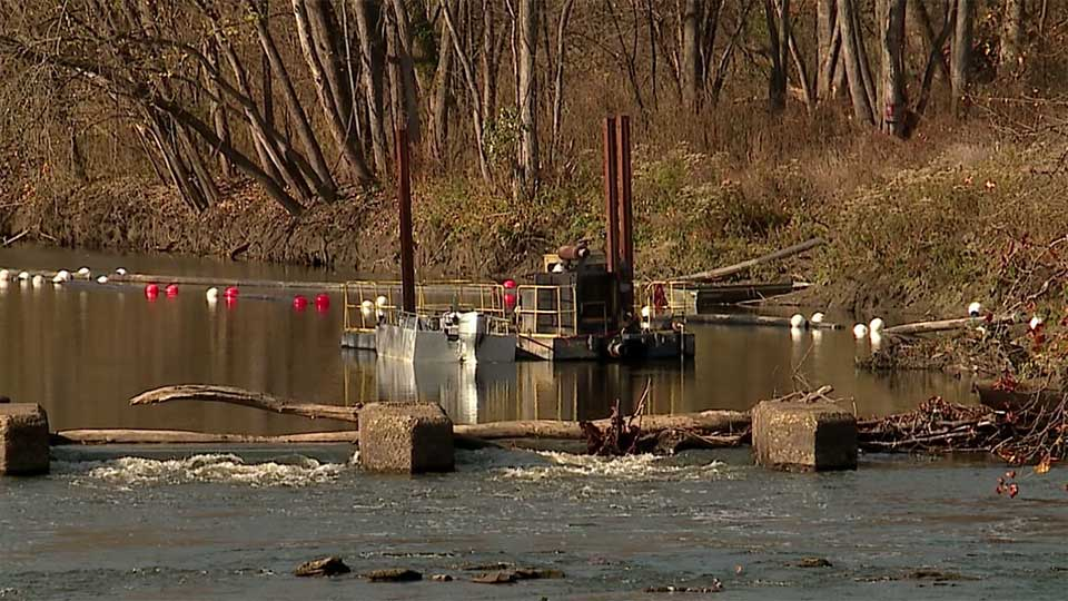 Friday afternoon, construction crews lowered a barge into the river in Lowellville where the dam will eventually be removed.