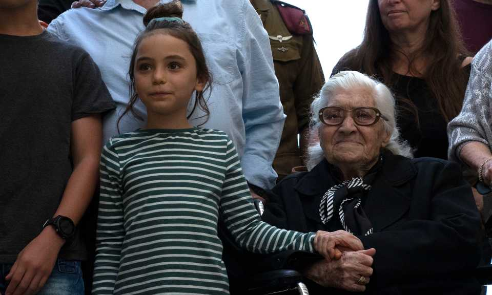 Melpomeni Dina holds the hand of an Israeli girl during a reunion at the Yad Vashem Holocaust memorial in Jerusalem, Sunday, Nov. 3, 2019. Dina, a 92-year-old Greek woman who rescued a Jewish family during the Holocaust has been reunited with two of the people she saved and dozens of their family members. Once a regular ritual, such reunions are quickly disappearing due to the advanced age of the rescuers and survivors.