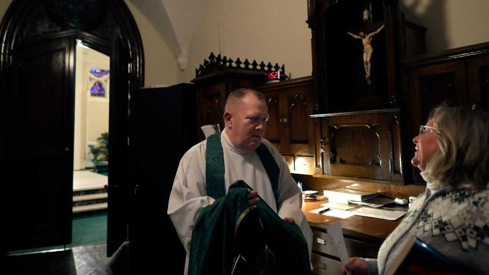 Rev. Mark Stelzer, a professor and chaplain at College of Our Lady of the Elms, speaks with sacristan Marlene Czepiel, right, in the sacristy before offering Mass in the school's chapel, in Chicopee, Mass. (AP Photo/Steven Senne)