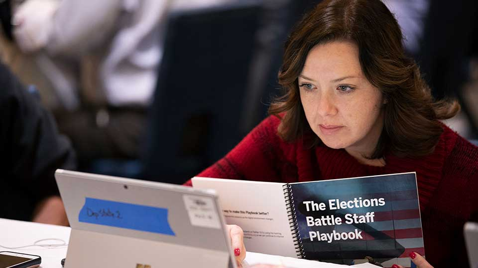 In this Monday, Dec. 16, 2019, photo, Mandy Vigil, from New Mexico, works during an exercise run by military and national security officials, for state and local election officials to simulate different scenarios for the 2020 elections, in Springfield, Va. These government officials are on the front lines of a different kind of high-stakes battlefield, one in which they are helping to defend American democracy by ensuring free and fair elections.