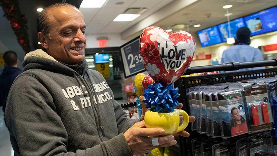In this Tuesday, Dec. 3, 2019, photo, Mohammed Hafar buys a gift for his daughter Jana Hafar while waiting for her flight at JFK Airport in New York. Jana had been forced by President Donald Trump's travel ban to stay behind in Syria for months while her father, his wife and son Karim started rebuilding their lives in Bloomfield, N.J., with no clear idea of when the family would be together again. Mohammed was part of a federal lawsuit filed in August of this year over the travel ban waiver process.