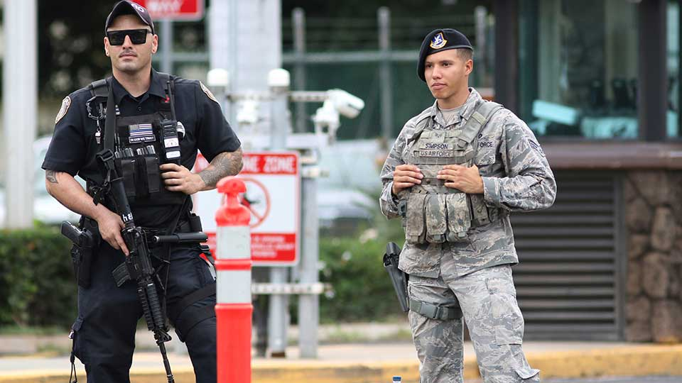 Security stands guard outside the main gate at Joint Base Pearl Harbor-Hickam, in Hawaii, Wednesday, Dec. 4, 2019. A shooting at Pearl Harbor Naval Shipyard in Hawaii left at least one person injured Wednesday, military and hospital officials said. Joint Base Pearl Harbor-Hickam spokesman Charles Anthony confirmed that there was an active shooting at Pearl Harbor Naval Shipyard.