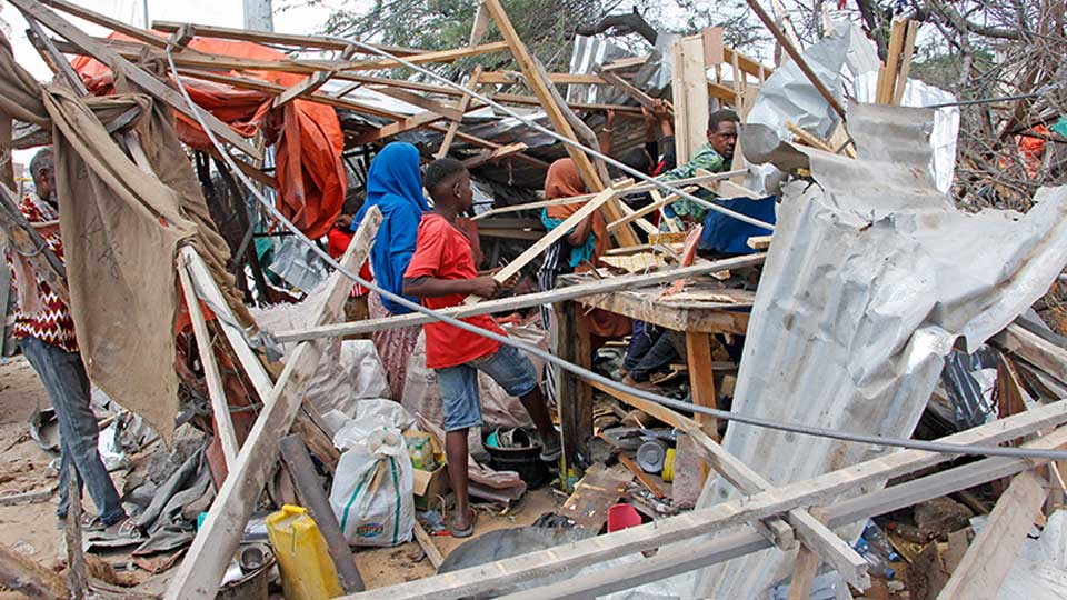 Somalis salvage goods after shops were destroyed in a car bomb in Mogadishu, Somalia, Saturday, Dec. 28, 2019. A truck bomb exploded at a busy security checkpoint in Somalia's capital Saturday morning, authorities said. It was one of the deadliest attacks in Mogadishu in recent memory.