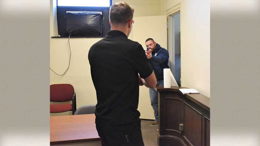 An officer of the Youngstown Police Department confronts new hire Thomas Fetherolf during a training exercise for new hires recently in the former municipal court facility in City Hall.