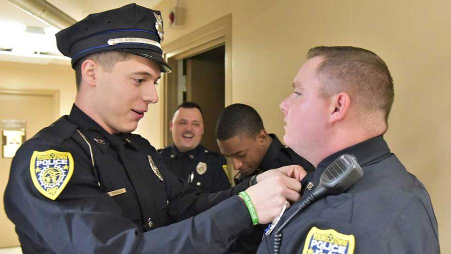 Bernard Fronzgalio, left, a new city police officer, helps fellow new officer Alex Wharry fix his tie just before their official portraits are taken on the fourth floor of the city police department.