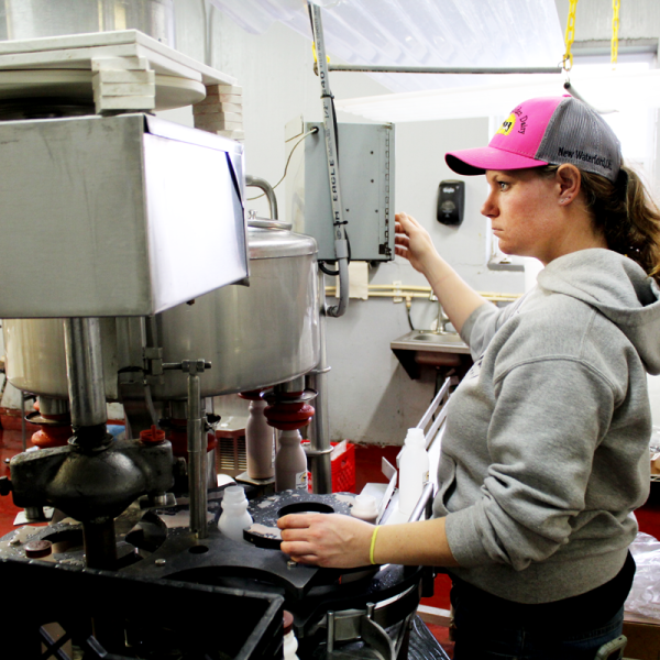 Kasey Baker adjusts the bottling machine in the on-farm milk plant at Baker's Golden Dairy in New Waterford, Ohio.