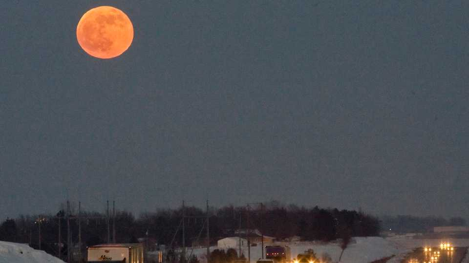 A blue moon rises over Interstate 80 west of Omaha, Neb., Thursday, Dec. 31, 2009. While not blue in color, the second full moon in a calendar month is called a Blue Moon.