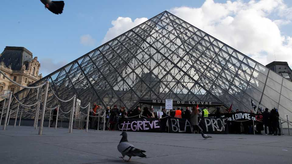 Pigeons fly by the Louvre pyramid as striking employees demonstrate outside the museum Friday, Jan. 17, 2020 in Paris. Paris' Louvre museum was closed Friday as dozens of protesters blocked the entrance to denounce the French government's plans to overhaul the pension system.