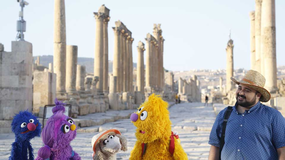 """This image released by Sesame Workshop shows, from left, Grover, Basma, Ma'zooza and Jad with Rami Delshad, who portrays Hadi in """"Welcome Sesame,"""" a new, locally produced Arabic TV program for the hundreds of thousands of children dealing with displacement in Syria, Iraq, Jordan and Lebanon."""