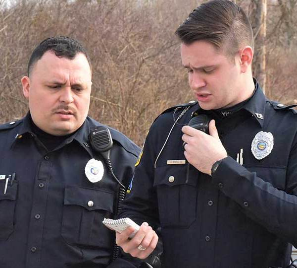 Youngstown police officer Dave Garcia, left, listens as officer John O'Neill Jr., right, runs a background check on a homeless man the pair found sleeping next to an abandoned building on Andrews Avenue. Garcia is one of five new officers who are being trained before hitting the streets on their own. O'Neill is Garcia's Field Training Officer.